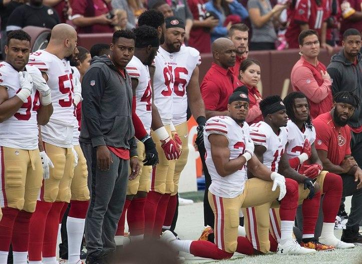 800px-San_Francisco_49ers_National_Anthem_Kneeling_(37721041581)
